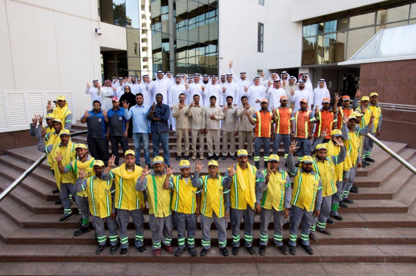 Dawood Al Hajiri, Director General of Dubai Municipality poses for photo with the workers on the International Worker's Day.
